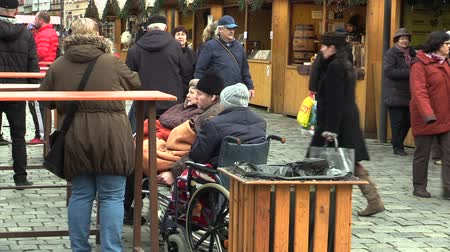 regret : OLOMOUC, CZECH REPUBLIC, NOVEMBER 17, 2017: Old people, people with disabilities in wheelchairs are in the Christmas markets square, health visitor