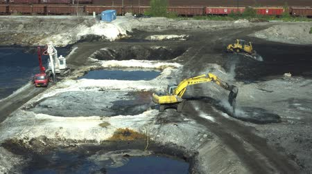 meio : OSTRAVA, CZECH REPUBLIC, AUGUST 28, 2018: Liquidation of remediation of landfills waste of oil and toxic substances, burnt lime is applied to oil pollution by means of fine cutter excavator bulldozer