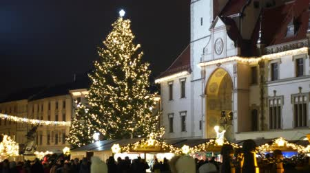 dobranoc : OLOMOUC, CZECH REPUBLIC, DECEMBER 20, 2018: Christmas tree luminous and shines beautiful decorated with golden ornaments and flasks, historical architectural city, market and goods stalls Wideo