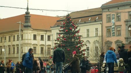 книжный магазин : BRNO, CZECH REPUBLIC, DECEMBER 21, 2018: Christmas tree luminous and shines beautiful decorated with golden ornaments and flasks red big, people and Jehovahs Witnesses and their books