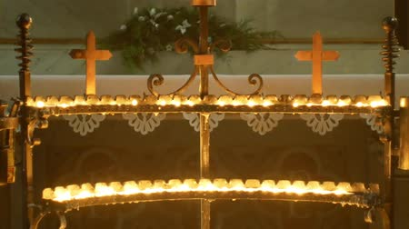 crucifixo : OLOMOUC, CZECH REPUBLIC, JANUARY 6, 2019: Burning candlelight with candles in the Catholic church, Sunday to three kings, candle fire flame church christian atmosphere after Holy Mass 4K