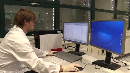resonantie : OLOMOUC, CZECH REPUBLIC, SEPTEMBER 28, 2018: Nuclear magnetic resonance NMR spectrometers, young scientist n pc with display monitor and charts, analysis genetic proton, proteins molecules