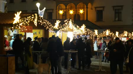 mulled wine : OLOMOUC, CZECH REPUBLIC, DECEMBER 20, 2018: Christmas markets night, illumination with ornaments stars and ornaments stall booth with alcohol punch with fruit juice, people buy drinks in a cup