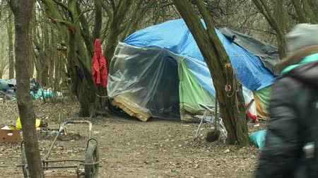 survivor : OLOMOUC, CZECH REPUBLIC, JANUARY 2, 2019: Sheets homeless ghetto tent and wood plastic foil chalet building lair people man poor living, wood burning, against rain and snow, life winter slam 4k Stock Footage
