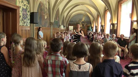 choral : OLOMOUC, CZECH REPUBLIC, APRIL 15, 2018: Choir choral children singing of sings Czech folk song, old people retirees sitting on chairs, gothic vaulted ceiling, Knights Hall city hall