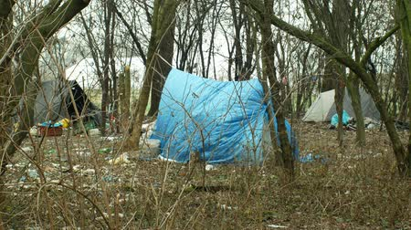 baita : OLOMOUC, CZECH REPUBLIC, JANUARY 2, 2019: Sheets homeless tents ghetto wood plastic foil chalet building lair people man poor living, wood burning, against rain and snow, life winter slam 4k