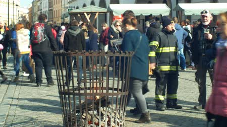 baca : OLOMOUC, CZECH REPUBLIC, FEBRUARY 29, 2019: Fire flames logs and wood with traditional iron crucible barrel, people walk around the square, folk stall market booths, Carnival Masopust Stok Video