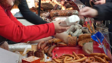 vendedora : OLOMOUC, CZECH REPUBLIC, FEBRUARY 29, 2019: Marketplace with stall products pig slaughter traditional household sausage, crowd of people shopping, weighs pate liver on scale, sausage-meat, sausage