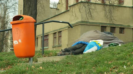 ümitsizlik : OLOMOUC, CZECH REPUBLIC, JANUARY 2, 2019: Authentic emotion homeless man senior asleep and sleep in sleeping bag on street near department store shopping centre shop, trash life city