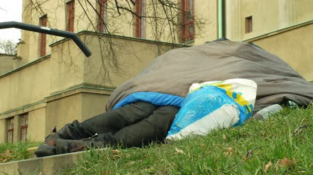 пробуждение : OLOMOUC, CZECH REPUBLIC, JANUARY 2, 2019: Awakening homeless lying on the ground in the park by another homeless, sleeping bag on street authentic emotion, life city park Стоковые видеозаписи