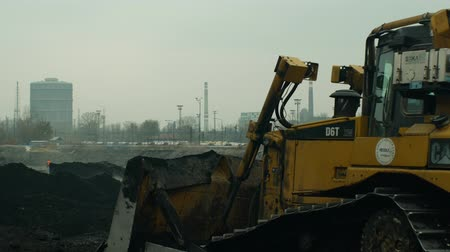 buldózer : OSTRAVA, CZECH REPUBLIC, NOVEMBER 28, 2018: Liquidation of remediation of landfills waste of oil and toxic substances, burnt lime is applied oil by means of fine excavator bulldozer, smog calamity Stock mozgókép