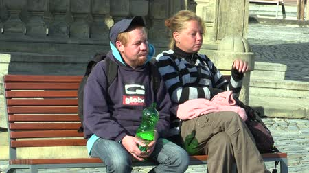 autêntico : OLOMOUC, CZECH REPUBLIC, SEPTEMBER 2, 2018: Authentic young man and woman homeless in city of street, holding a plastic bottle with white wine alcohol, town Olomouc, Moravia, Czech Republic, Europe