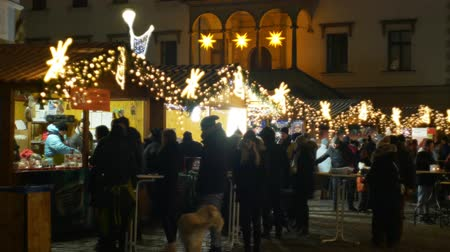 viennese : OLOMOUC, CZECH REPUBLIC, DECEMBER 20, 2018: Christmas markets night, illumination with ornaments stars and ornaments stall booth with alcohol punch with fruit juice, people buy drinks in a cup