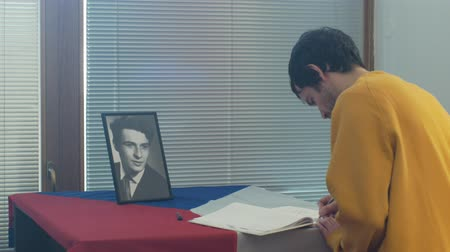 oppression : OLOMOUC, CZECH REPUBLIC, JANUARY 16, 2019: Jan Palach portrait student and flag Czech Republic, city hall room and historic in Olomouc, memorial book of the nations messages man writes authentic Stock Footage