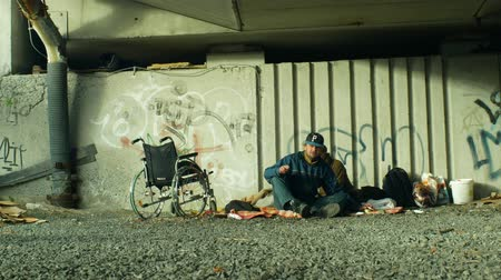 madriguera : OLOMOUC, CZECH REPUBLIC, OCTOBER 24, 2018: Authentic emotion group of homeless people and one wheelchair invalid without legs in place under a bridge where they sleep, Europe