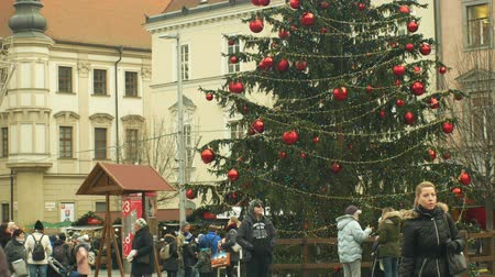 vasárnap : BRNO, CZECH REPUBLIC, DECEMBER 21, 2018: Christmas tree luminous and shines beautiful decorated with golden ornaments and flasks red big, time lapse people and children at the wooden bell tower