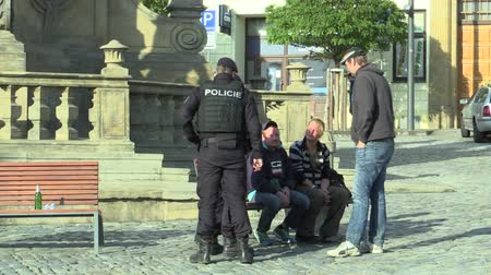 alkoholik : OLOMOUC, CZECH REPUBLIC, SEPTEMBER 2, 2018: Police solves the problem of the homeless on the plague column, drinking alcoholic beverages in public, police new car, conflict authentic, policemen