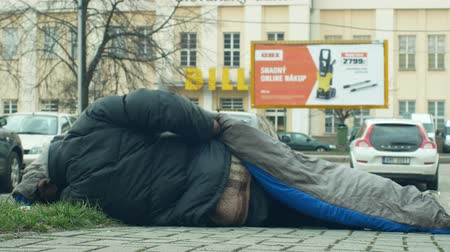 madriguera : OLOMOUC, CZECH REPUBLIC, JANUARY 2, 2019: Authentic emotion homeless man senior asleep and sleep in sleeping bag on street near department store shopping centre shop, walking people life city wind