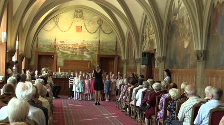 choral : OLOMOUC, CZECH REPUBLIC, APRIL 15, 2018: Choir choral children singing of sings Czech folk song Sly panenky silnici, old people retirees sitting on chairs, gothic vaulted ceiling