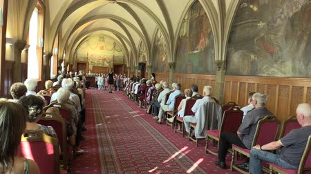 cerimonial : OLOMOUC, CZECH REPUBLIC, APRIL 15, 2018: Choir choral children singing of sings Czech folk song Sly panenky silnici, old people retirees sitting on chairs, gothic vaulted ceiling