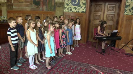 choral : OLOMOUC, CZECH REPUBLIC, APRIL 15, 2018: Choir chorus children singing of the sings Czech old folk song Okolo Hradce, emotional human speech and emotion, Knights Hall in the town city hall