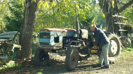 mítosz : OLOMOUC, CZECH REPUBLIC, OCTOBER 24, 2018: Stark historical home made tractor, farmers in the village are home-made, man gives the car a battery to the engine, autumn period and colors Stock mozgókép