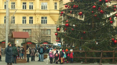 domingo : BRNO, CZECH REPUBLIC, DECEMBER 21, 2018: Christmas tree luminous and shines beautiful decorated with ornaments and flasks, children at wooden bell tower, joy of kindergarten bell ring Stock Footage