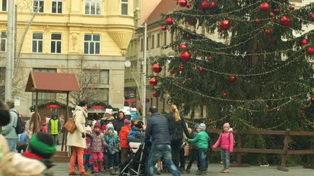 domingo : BRNO, CZECH REPUBLIC, DECEMBER 21, 2018: Christmas tree luminous and shines beautiful decorated with ornaments and flasks, children at wooden bell tower, joy of kindergarten bell ring, xmas ball Stock Footage