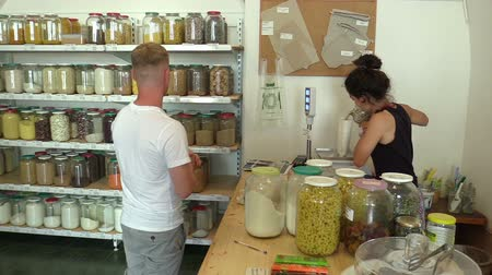 a small bottle : PRAGUE, CZECH REPUBLIC, MAY 25, 2019: Shop organic food raw materials without packaging, people choosing and buy healthy cereals, legumes, dried fruits, store reusing bags