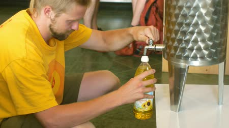gıda maddesi : PRAGUE, CZECH REPUBLIC, MAY 25, 2019: Sunflower oil organic quality bio, steel barrel or bowl, for cold food and fried foodstuff, the man pours gold oil in the store shop
