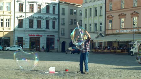 preciso : OLOMOUC, CZECH REPUBLIC, JUNE 11, 2019: Making bubbles using detergent soap and rope on chopsticks, big bubble, street arts man wind performs street and begging money, soapy performer