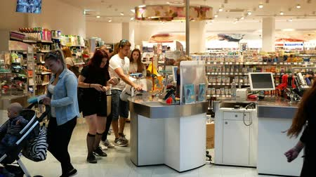 dispensary : PRAGUE, CZECH REPUBLIC, MAY 25, 2019: European people with shopping of drugstore chemists shop, ticket office with a young woman, going from the shopping center, payment of money