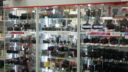 fotográfico : PRAGUE, CZECH REPUBLIC, MAY 25, 2019: Photographic and video technology professional and modern cameras lenses, accessories in luxury glass cabinets in business house and shop