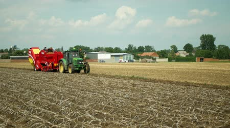 OLOMOUC, CZECH REPUBLIC, AUGUST 9, 2019: Potato harvesting in the field with a special harvester machine Grimme modern equipment with people farmers sorting potatoes and tractor John Deere, Europe