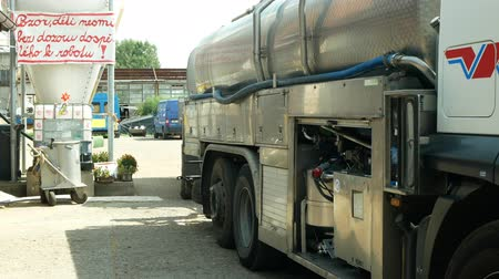 čeština : OLOMOUC, CZECH REPUBLIC, MAY 25, 2019: Milk tank leaves pumped with milk from farm, truck village farming, freight transport trailer trucking, technician servicing manual worker