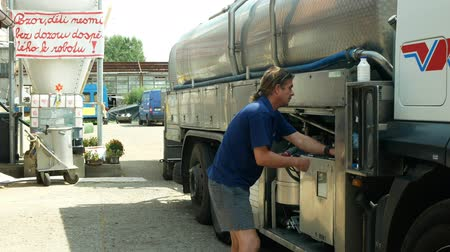 servicing : OLOMOUC, CZECH REPUBLIC, MAY 25, 2019: Milk tank leaves pumped with milk from farm, truck village farming, freight transport trailer trucking, technician servicing manual worker