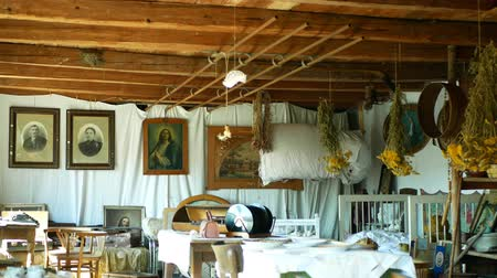 parasztház : OLOMOUC, CZECH REPUBLIC, SEPTEMBER 5, 2019: Traditional Moravia cottage old folk Hana with table and dried herbs. Interior of peasant bed and clay pots unique hut. Christian paintings