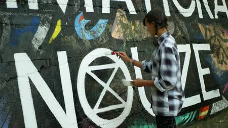 ekspres : OLOMOUC, CZECH REPUBLIC, SEPTEMBER 22, 2019: Activist woman paints and repainting symbol Extinction Rebellion climate emergency on legal wall for graffiti, action demonstration Stok Video