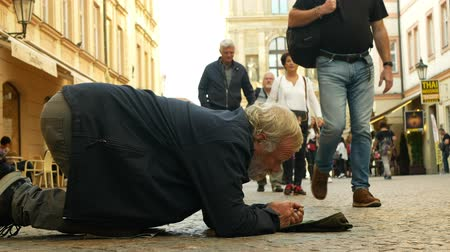 alms : PRAGUE, CZECH REPUBLIC, SEPTEMBER 9, 2019: Homeless begging tourists throw coin money into baseball cap and recalculates money, begs alms kneeling or kneel street life authentic beggar Stock Footage