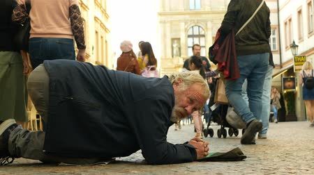 alms : PRAGUE, CZECH REPUBLIC, SEPTEMBER 9, 2019: Homeless begging tourists coin money into baseball cap and recalculates money, begs alms kneeling or kneel street life authentic beggar Stock Footage