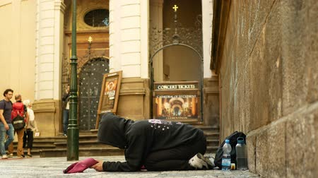 ajoelhado : PRAGUE, CZECH REPUBLIC, SEPTEMBER 9, 2019: Homeless girl begging tourists throw coin money into baseball cap, begs alms kneeling or kneel street life authentic Prague beggar