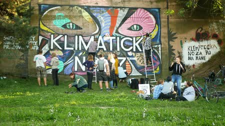 протест : OLOMOUC, CZECH REPUBLIC, SEPTEMBER 22, 2019: Activist people paints and repainting symbol Extinction Rebellion climate emergency on legal wall for graffiti, action demonstration