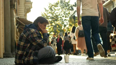 PRAGUE, CZECH REPUBLIC, SEPTEMBER 9, 2019: Homeless begging Asian tourists throw coin money into cup and recalculates money, begs alms kneeling or kneel street life authentic Wideo