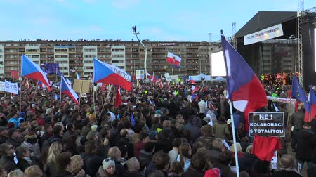 comunismo : PRAGUE, CZECH REPUBLIC, NOVEMBER 16, 2019: Demonstration people crowd against Prime Minister Andrej Babis demise, 300,000 mass protesters throng Letna Prague, flags and banners, Mikulas Minar activist Stock Footage