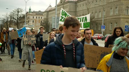 korumak : OLOMOUC, CZECH REPUBLIC, NOVEMBER 30, 2019: Activists students, Friday for future, demonstration against climate change, banner sign the climate is rising and thats our planet, people crowd Stok Video