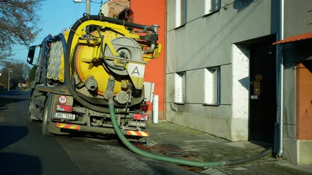 OLOMOUC, CZECH REPUBLIC, DECEMBER, 30, 2019: Septic cesspool emptying pumping into pipe tank truck suction hose under pressure. sump contains pollution sludge sewage water, people houses village