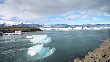 Iceland Jokulsarlon glacier lagoon the water flowing to the ocean together with small piece of iceberg. Stok Video