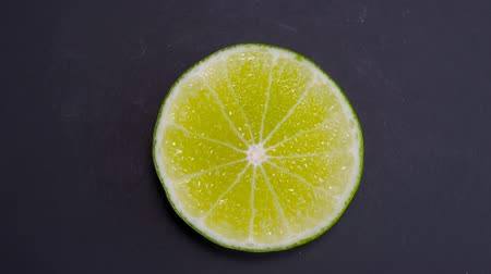 citron : Lime Sliced Rotation Full HD video. Green Fresh citrus on Black Background Stock Footage