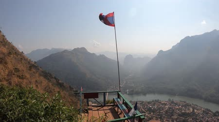none : Laos flag at Nang None peak overlooking Nam Ou river and Nong Khiaw village in Laos Stock Footage
