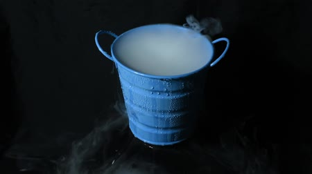 Abstract dry ice movement in the blue bucket on darkness background